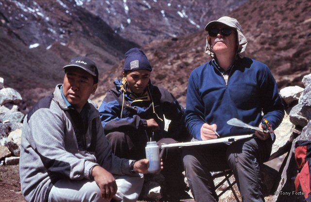 Tony Foster working on a small painting above Namche Bazaar, aided by Ang Phuri Sherpa and assistant. © 2005 Mike Nathan